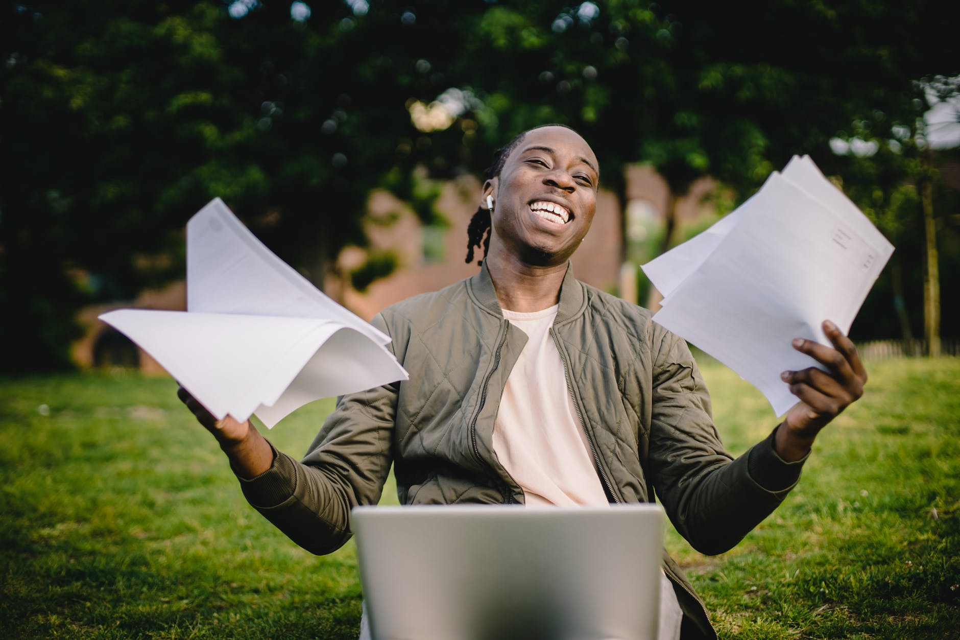 happy african american man holding sheets of paper in front of laptop